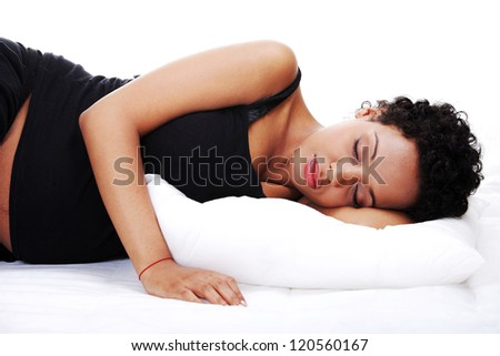 Pregnant woman sleeping on bed - stock photo