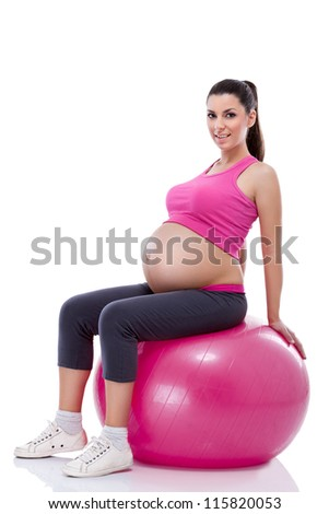 pregnant woman sportswear with large belly  sitting on fitness ball - stock photo