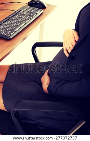 Pregnant woman touching her belly in the office - stock photo