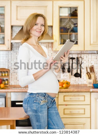 pregnant woman using a digital tablet - stock photo