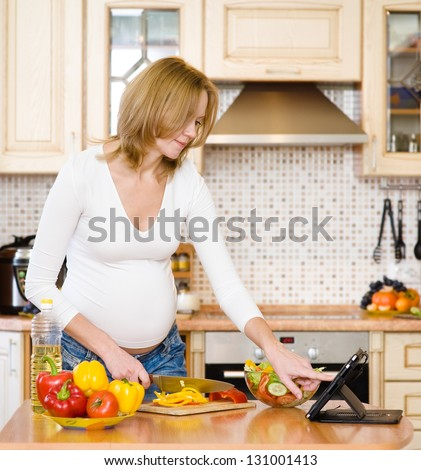 pregnant woman using a tablet computer to cook in her kitchen - stock photo