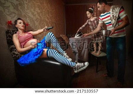Pregnant woman watching TV, while her daughter irons a shirt and her husband cooking in the living room - stock photo