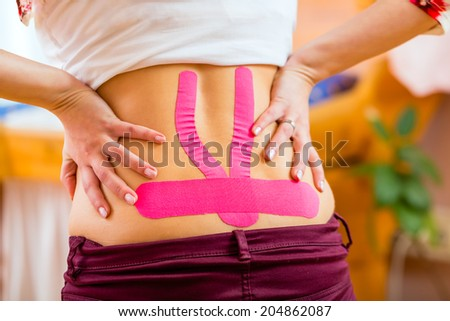 Pregnant woman wearing Kinesio-Tape against back pain - stock photo