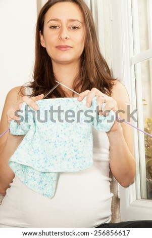 pregnant woman who knitted baby clothes - stock photo