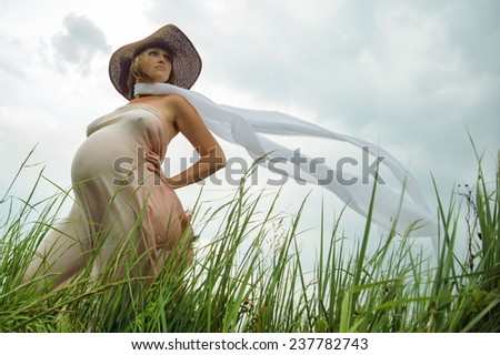 Pregnant woman with a big belly in a hat and scarf in developing the park in open space. - stock photo