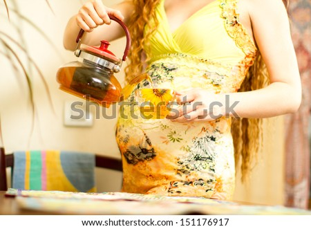 Pregnant woman  with a cap of tea on kitchen. The concept of drinking and a healthy lifestyle - stock photo
