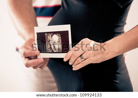 pregnant woman with a photo of the ultrasound - stock photo