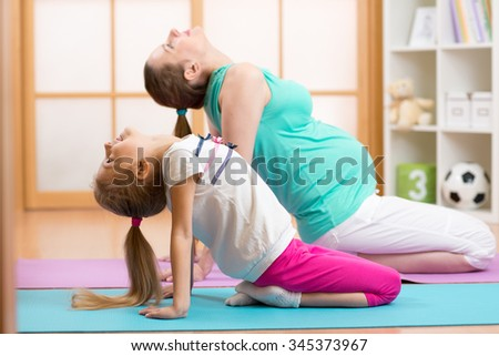 Pregnant woman with elder child daughter doing gym fitness exercise - stock photo