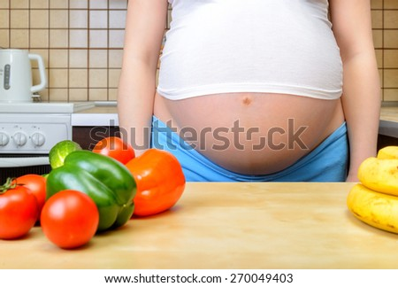 Pregnant woman with fresh vegetables in the kitchen - stock photo