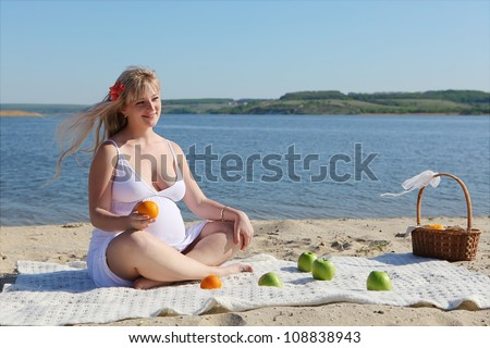 Pregnant woman with fruits sitting on the beach - stock photo