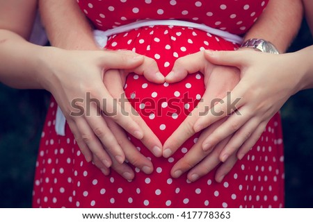 Pregnant woman with her hands on her belly - stock photo
