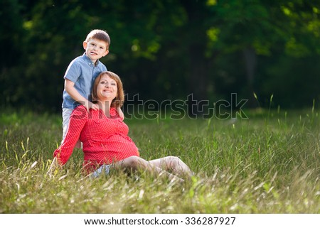 Pregnant woman with her son relaxing in park - stock photo