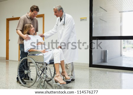 Pregnant woman with in wheelchair with partner talks to doctor in the hospital corridor - stock photo