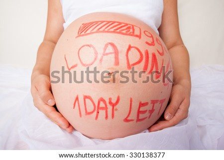 Pregnant woman with loading concept painted on her belly - stock photo