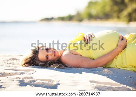 Pregnant woman with long hair in yellow dress lying down on the beach - stock photo