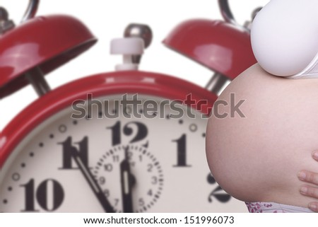 pregnant woman with naked belly and alarm clock / pregnancy - stock photo