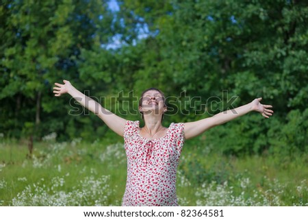 Pregnant woman with open hands in the forest - stock photo