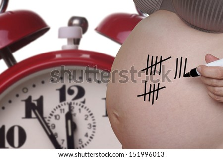 pregnant woman with pen and tally sheet on the belly / pregnancy - stock photo