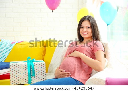 Pregnant woman with presents at baby shower party - stock photo