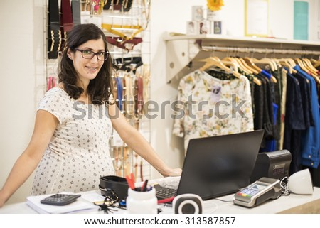 Pregnant woman working in clothes store near to computer - stock photo