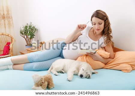 Pregnant woman writing notes with golden retriever puppy at home - stock photo