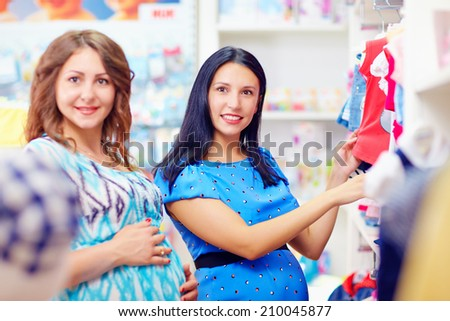 pregnant women buying clothes for babies - stock photo