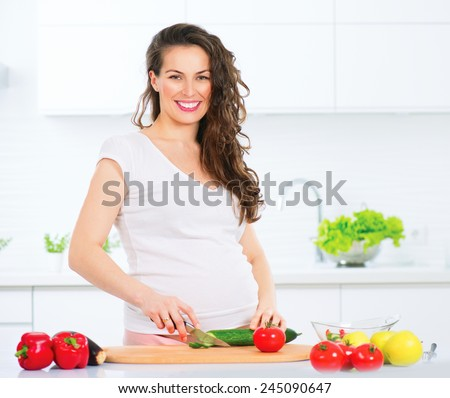 Pregnant Young Woman Cooking vegetables. Healthy Food - Vegetable Salad. Diet. Dieting Concept. Healthy Lifestyle. Cooking At Home. Prepare Food - stock photo