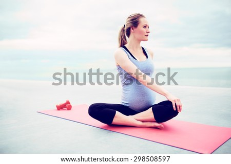 Pregnant young woman doing fitness exercises sitting cross legged on a gym mat twisting her body to strengthen her stomach and back muscles - stock photo
