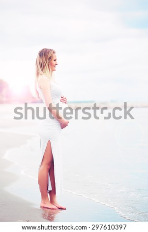 Pregnant young woman enjoying a day at the sea standing barefoot at the edge of the surf cradling her swollen stomach as she looks out to sea in a fitness concept - stock photo