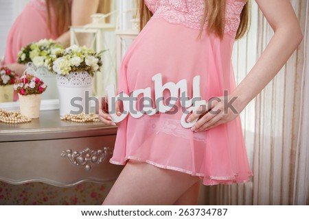 pregnant young woman in soft fluffy bathrobe pregnant girl tenderly embraces his tummy pregnant girl in transparent beautiful pink nightgown reflection in the mirror - stock photo