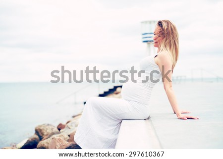 Pregnant young woman relaxing at the seaside sitting on a promenade overlooking the ocean in a white maternity dress, side view emphasising her swollen belly - stock photo