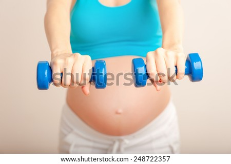 Prenatal exercises. Beautiful pregnant woman exercising stretching while sitting on mat - stock photo