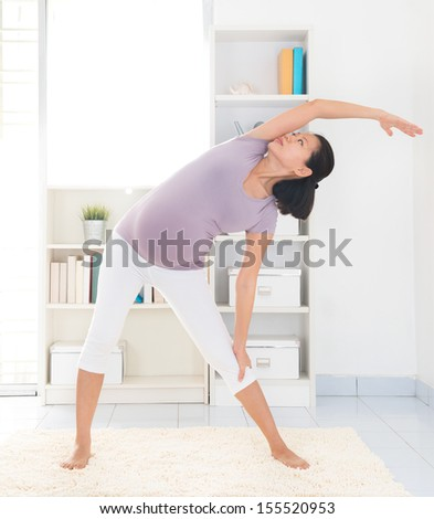 Prenatal yoga. Full length healthy 8 months pregnant calm Asian woman meditating or doing yoga exercise at home. Relaxation yoga side stretching pose. - stock photo