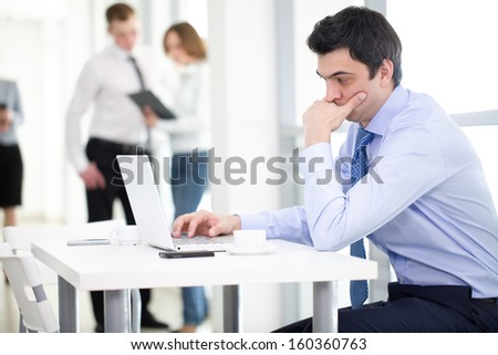 preoccupied businessman with colleagues in the background - stock photo