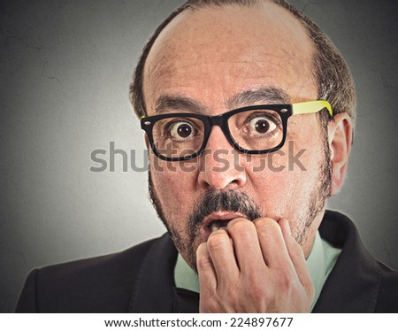 Preoccupied middle aged man. Closeup portrait nerdy guy with glasses biting his nails looking at you craving something anxious isolated grey wall background. Human face expression emotion feeling - stock photo