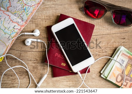 Preparation for travel, cell phone, money, passport, road map on wooden table - stock photo