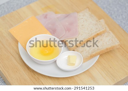preparation fresh eggs ,bacon ,cheese and bread with butter in dish - stock photo