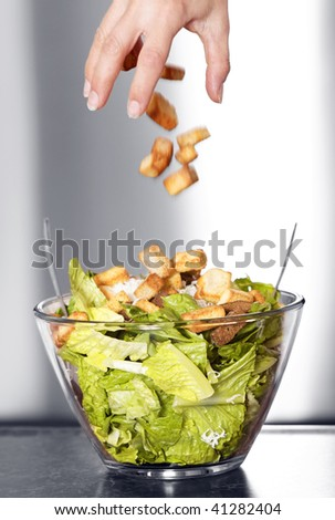 Preparation of a caesar salad in a glass bowl. Movement blur of crouton falling in the salad. Selective black and white with shallow depth of field. - stock photo