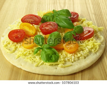Preparation of a vegetarian pizza with cherry tomatoes - stock photo