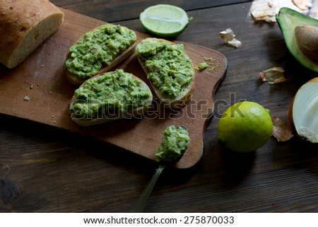 preparation of avocado guacamole in process all ingredients on table lime, onion, avocado all organic and fresh on dark wood rustic style background with ready guacamole on a ciabatta bread soft focus - stock photo