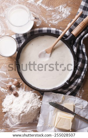 Preparation of bechamel sauce in a pan and ingredients on the table. vertical top view close-up