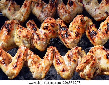 preparation of chicken wings on a fire - stock photo