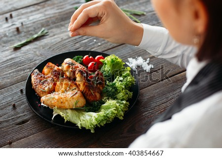 Preparation of chicken wings on wooden table. Chief cooks grilled spicy chicken with fresh vegetables. Over the shoulder view of food preparation.  - stock photo