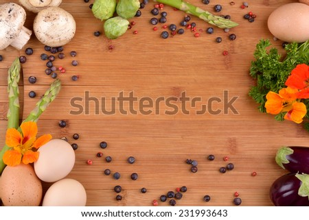 Preparation of egg, mushrooms, asparagus, mini eggplant, brussels sprouts on bamboo board. - stock photo