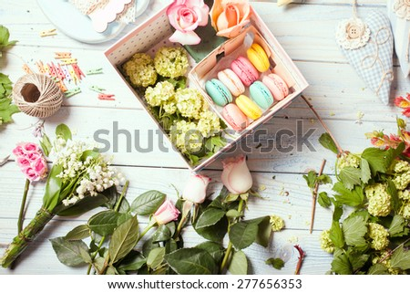 Preparation of flower box with macaroons, top view of florist workplace - stock photo