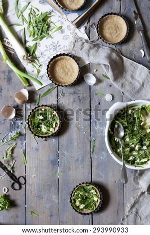 Preparation of little quiche with fresh ingredients on wooden rustic surface - stock photo