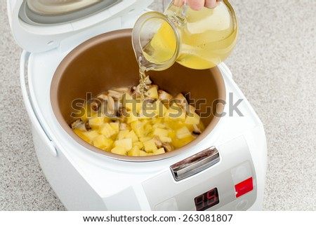 preparation of mushroom soup with added chicken broth in multicooker closeup - stock photo