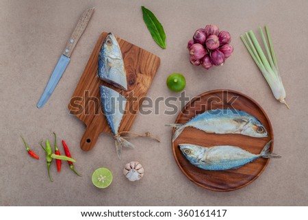 Prepare cooking traditional thai food preserved salted fish salad with chili ,onion,lime, Cilantro ,garlic and lemongrass on brown paper board. - stock photo