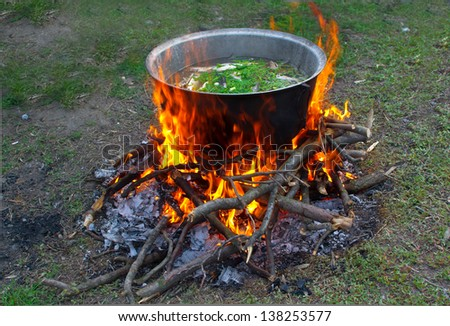 prepare tasty food over a campfire - stock photo