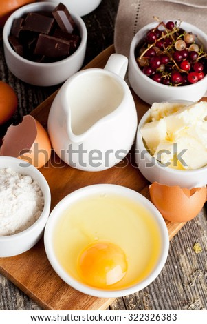 prepared baking ingredients on wooden table, vertical, close up - stock photo